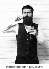 handsome bearded man with long beard and mustache has stylish hair on serious face holding glass of alcoholic beverage in vintage suede leather waistcoat on white brick wall studio background.