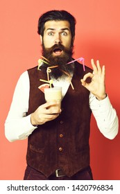 handsome bearded man with long beard and mustache has stylish hair on surprised face holding glass of alcoholic beverage in vintage suede leather waistcoat on red studio background.