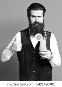 handsome bearded man with long beard and mustache has stylish hair on serious face holding glass of alcoholic cocktail in vintage suede leather waistcoat on red studio background.