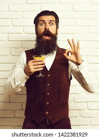 handsome bearded man with long beard and mustache has stylish hair on surprised face holding glass of alcoholic beverage in vintage suede leather waistcoat o white brick wall studio background.