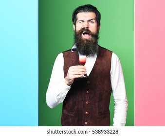 handsome bearded man with long beard and mustache has stylish hair on funny face holding glass of alcoholic shot in vintage suede leather waistcoat on colorful studio background, copy space
