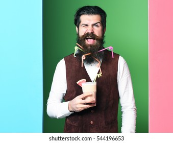 handsome bearded man with long beard and mustache has stylish hair on smiling face holding glass of alcoholic beverage in vintage suede leather waistcoat on colorful studio background