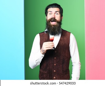 handsome bearded man with long beard and mustache has stylish hair on happy face holding glass of alcoholic shot in vintage suede leather waistcoat on colorful studio background, copy space