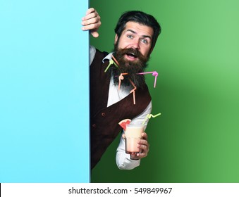 handsome bearded man with long beard and mustache has stylish hair on smiling face holding glass of alcoholic beverage in vintage suede leather waistcoat on blue green studio background, copy space
