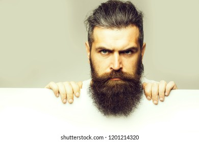 handsome bearded man with long lush beard and moustache on sad face with white paper sheet in studio on grey background, copy space