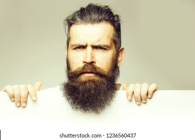 handsome bearded man with long lush beard and moustache on thougtful face with white paper sheet in studio on grey background, copy space