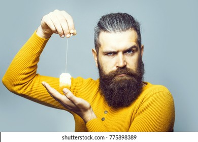 handsome bearded man with long lush beard and moustache on serious face holding tea bag in yellow shirt in studio on grey background