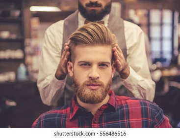 Handsome bearded man is looking at camera while getting haircut by hairdresser at the barbershop