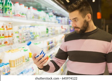 Handsome bearded man looking shocked holding an expensive product while shopping groceries at the supermarket price poverty luxury shopper buying expressing emotional surprised shock high pricing