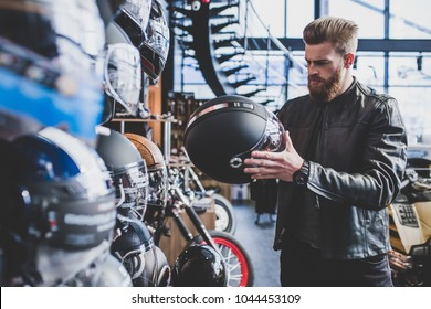 Handsome bearded man in motorcycle shop. Biker is choosing new vehicle and motorcycle accessories. Helmets on wooden background. Safety driving concept.