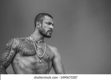 Handsome bearded man. Muscular latin lover. Latin Man with muscular body looks seriously. Handsome brutal man on blue sky background. Portrait of brutal handsome male model