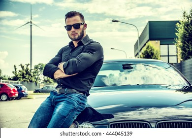 Handsome bearded man on polished car in sunglasses