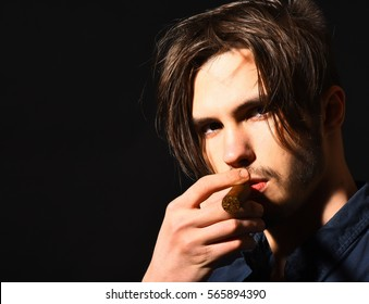 handsome bearded man portrait in blue shirt with stylish hair on serious face smoking cigar in black studio background, copy space