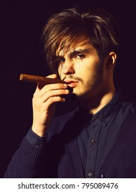 handsome bearded man portrait in blue shirt with stylish hair on serious face smoking cigar in black studio background