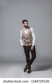 handsome bearded man posing in elegant stylish waistcoat on grey