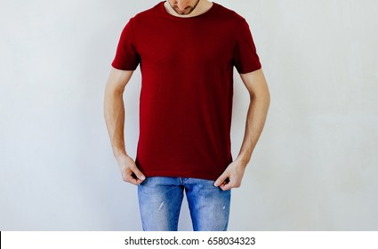 Handsome bearded man in red blank t-shirt looking down and standing on the cement wall background with space to copy paste