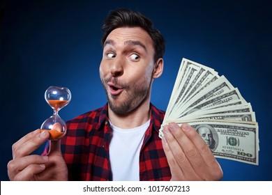 Hombre guapo con barba y camisa roja con dinero y reloj de arena. Un tipo gracioso es una ganadora afortunada, ella tiene un montón de dinero y un reloj de arena, está feliz de ganar un bote de un millón de dólares, el tiempo es dinero.