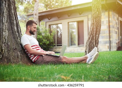Handsome bearded man is sitting in the backyard under the tree with his laptop
