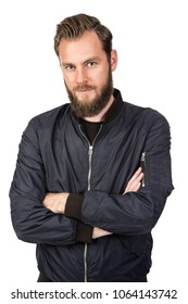 Handsome bearded man standing against a white background wearing a black tshirt and blue jacket in jeans with arms crossed. Looking at camera.