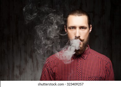 Handsome bearded man is standing and breathing out smoke. He is looking forward seriously. Copy space in left side