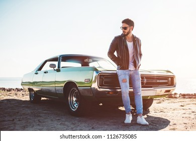 Handsome bearded man is standing near his green retro car on the beach. Vintage classic car.