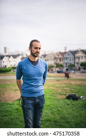 Handsome and bearded man standing on The Painted Ladies of San Francisco, California