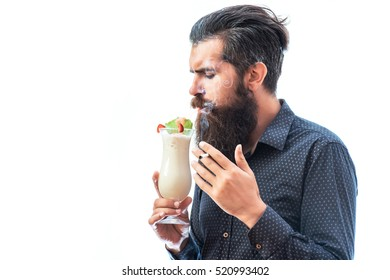 handsome bearded man with stylish hair mustache and beard on serious face holding glass of nonalcoholic beverage and smoking cigarette isolated on white, copy space