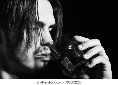 handsome bearded man with stylish hair on serious face holding and drink whisky in black studio background, close up