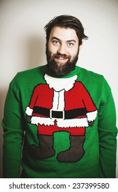 Handsome bearded man in stylish Santa Claus pullover smiling at Christmas and New Year party