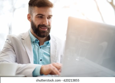 Handsome bearded man in stylish white and blue suit works on computer.