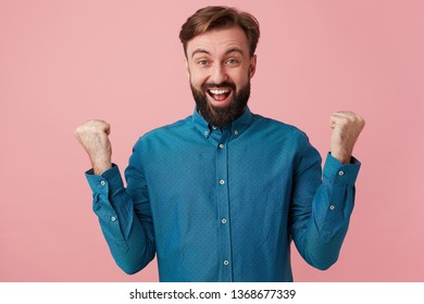 Handsome bearded man suddenly turns out to be a winner, gets a victory, triumphs, happy surprised holds his hands up his fists clenched, overflowing with joy and happiness,over pink background