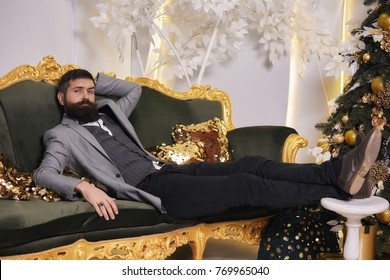 Handsome bearded man in suit relax on luxurious couch eve New year. Elegant male in luxury apartments waiting Christmas. Brutal bearded man sitting in comfortable sofa. Arrogant rich man, bisnessman.