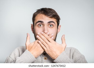 handsome bearded man surprised and closes his mouth with his hands, close-up on the background