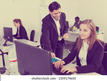 Handsome bearded man talking and flirting with attractive smiling woman working at a co-working space