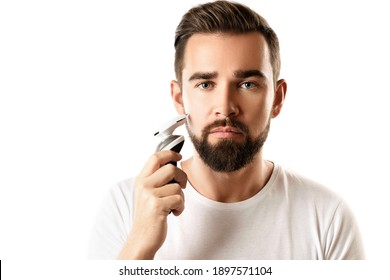 Handsome bearded man is using electric trimmer on white background