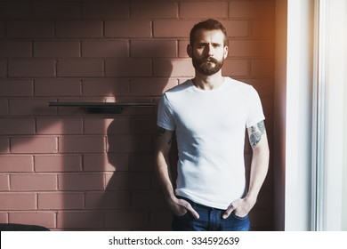 handsome bearded man wearing blank white t-shirt on brick wall background