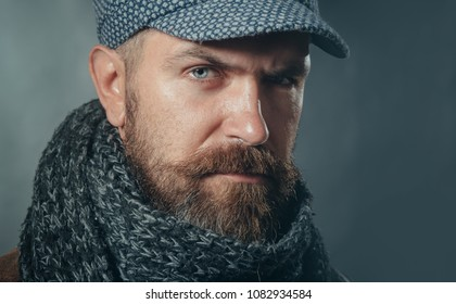 Handsome bearded man wearing demi-season clothing. Serious man with beard, brutal caucasian hipster in warm scarf wrapped around his neck, hat on head and jacket. Advertise autumn-winter fashion.