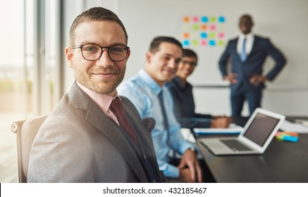 Handsome bearded man wearing suit and tie with three professional co-workers in meeting at conference table in front of a large white board