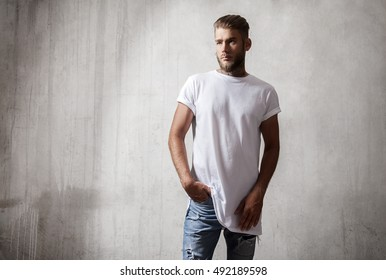 Handsome bearded man in white blank t-shirt standing on the cement wall background