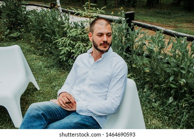 Handsome bearded man in white sitting on chair in garden and holding cigarette
