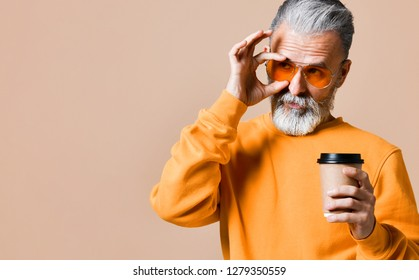 handsome bearded man in a yellow sweatshirt and trendy yellow glasses with paper cup of morning coffee