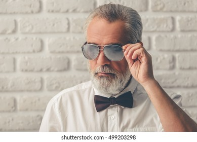 Handsome bearded mature gentleman in formal suit and bow tie is adjusting his sun glasses, on a white brick wall background