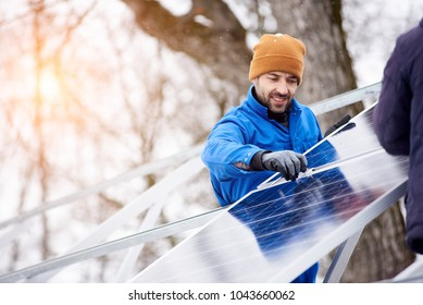 Handsome bearded mature male electrician worker smiling while installing solar pannels on power plant factory copyspace occupation working professionalism confidence job profession environment energy.