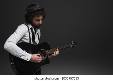 handsome bearded musician playing acoustic guitar on black