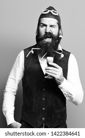 handsome bearded pilot or aviator man with long beard and mustache on funny face tasting glass of alcoholic shot in vintage suede leather waistcoat with hat and glasses on blue studio background.