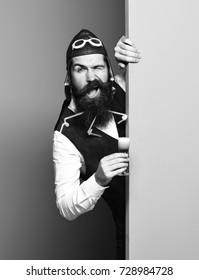 handsome bearded pilot or aviator man with long beard and mustache on funny face holding glass of alcoholic shot in vintage suede leather waistcoat with hat and glasses on blue green studio background