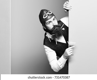 handsome bearded pilot or aviator man with long beard and mustache on serious face holding glass of alcoholic beverage in vintage suede leather waistcoat with hat and glasses on studio background
