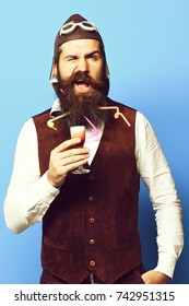 handsome bearded pilot or aviator man with long beard and mustache on funny face tasting glass of alcoholic shot in vintage suede leather waistcoat with hat and glasses on blue studio background