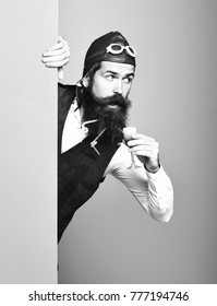 handsome bearded pilot man with long beard and mustache on surprised face holding glass of alcoholic shot in vintage suede leather waistcoat with hat and glasses on colorful studio background