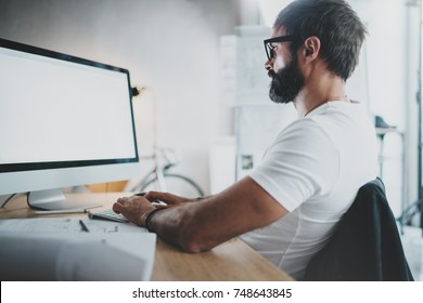 Handsome bearded professional architect wearing eye glasses working at modern loft studio-office with desktop computer.White blank display screen.Blurred background. Horizontal